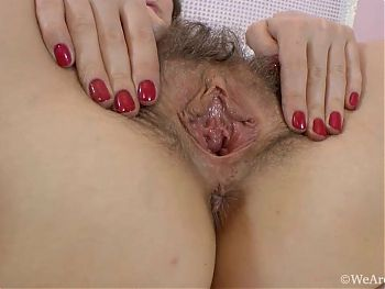 Hairy MILF Agneta oils up her breasts and strips on her bed