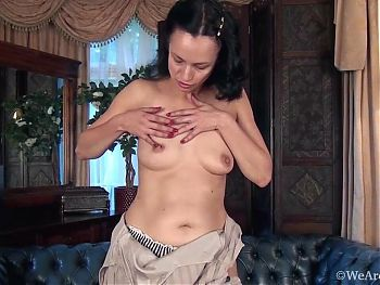 Hairy mature Tracey Anne playing naked on the sofa